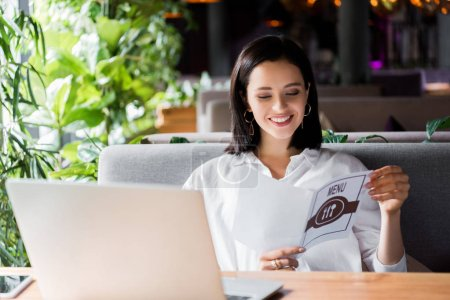 Photo for Happy woman holding menu near laptop in restaurant - Royalty Free Image