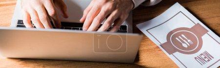 Photo pour Prise de vue panoramique de la femme tapant sur ordinateur portable près du menu sur la table - image libre de droit
