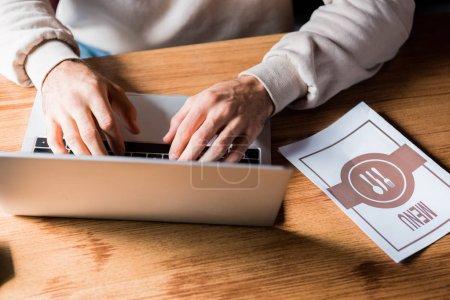 Photo pour Vue recadrée de la femme tapant sur ordinateur portable près du menu sur la table - image libre de droit