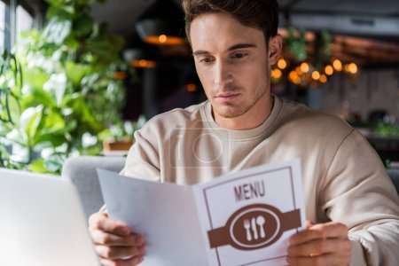 Photo for Selective focus of handsome man holding menu in restaurant - Royalty Free Image