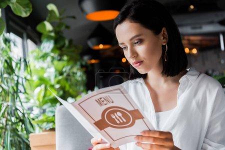 Photo pour Une jeune femme séduisante regardant le menu au restaurant - image libre de droit