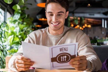 Photo pour Sélectivité de l'homme heureux regard sur le menu du restaurant - image libre de droit