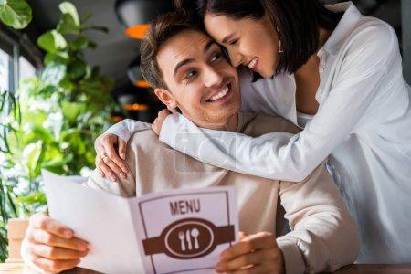 Photo pour Femme heureuse étreignant homme gai avec menu au restaurant - image libre de droit