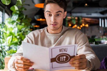 Photo pour Focus sélectif de l'homme surpris tenant menu au restaurant - image libre de droit