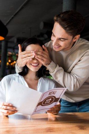 Photo pour Heureux homme fermer les yeux de gai femme tenant menu dans le restaurant - image libre de droit