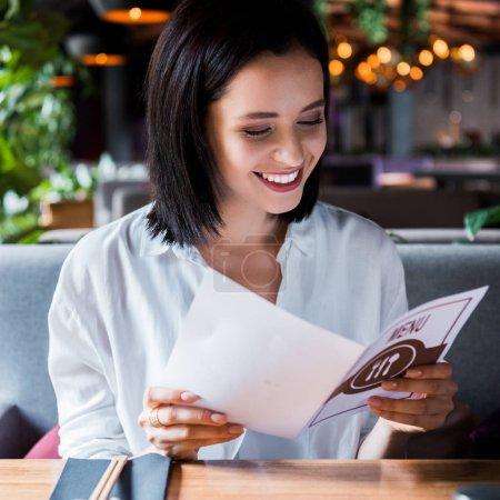 Photo pour Focalisation sélective de la joyeuse femme assise dans un bar à sushis et regardant le menu - image libre de droit