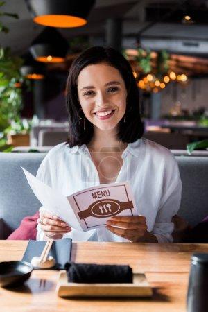 Photo pour Sélectivité de la femme gaie assise au restaurant et tenant le menu - image libre de droit