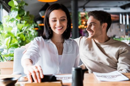Photo for Selective focus of happy woman taking napkin near man in sushi bar - Royalty Free Image