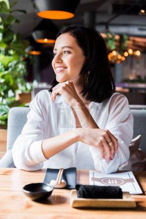 Photo pour Foyer sélectif de femme gaie assise dans le restaurant - image libre de droit