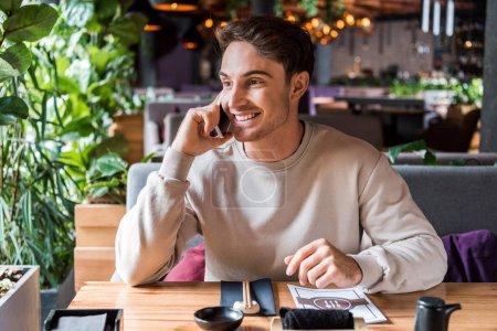 Photo pour Homme gai parlant sur smartphone et souriant dans le bar à sushi - image libre de droit