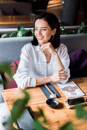 Photo pour Foyer sélectif de femme heureuse assise dans le restaurant - image libre de droit
