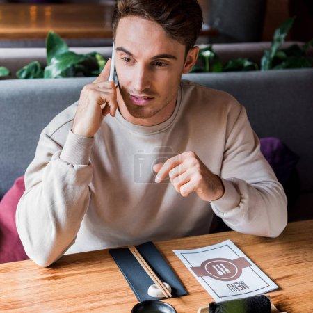 Photo pour Bel homme parlant sur smartphone dans le bar à sushi - image libre de droit