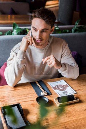 Photo pour Foyer sélectif de bel homme parlant sur smartphone dans le bar à sushi près de la table avec menu - image libre de droit