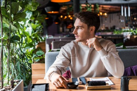 Photo for Handsome man sitting in sushi bar near table with menu - Royalty Free Image