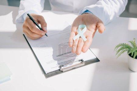 Photo pour Crochet vu d'un médecin tenant un ruban bleu pendant qu'il rédigeait un rapport médical - image libre de droit