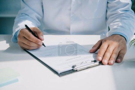 Photo pour Vue partielle du médecin écrivant le diagnostic dans le rapport médical sur le presse-papiers - image libre de droit