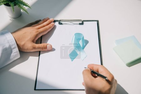 Photo pour Vue partielle du médecin écrivant le diagnostic sur le presse-papiers près du ruban bleu de sensibilisation - image libre de droit