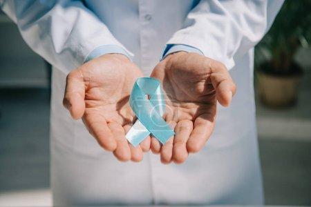 Photo pour Crochet vue d'un médecin en manteau blanc tenant un ruban bleu de sensibilisation - image libre de droit