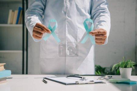 Photo pour Vue partielle du médecin en manteau blanc tenant des rubans bleus de sensibilisation - image libre de droit