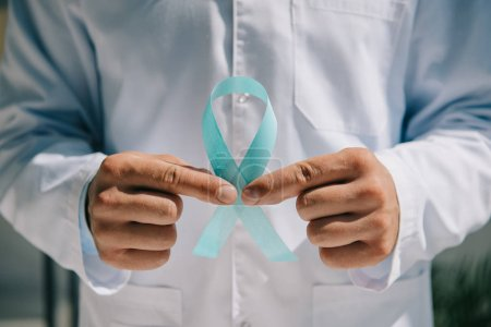 Photo for Partial view of doctor in white coat holding blue awareness ribbon - Royalty Free Image