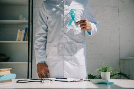 Photo pour Vue partielle d'un médecin en manteau blanc tenant un ruban bleu de sensibilisation tout en se tenant près d'un bureau - image libre de droit