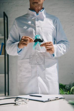 Photo pour Vue partielle d'un médecin en manteau blanc tenant un ruban bleu de sensibilisation avec de la moustache coupée en papier - image libre de droit