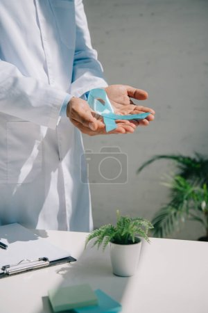 Photo for Cropped view of doctor holding blue awareness ribbon near table with clipboard and flowerpot - Royalty Free Image