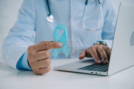 Photo pour Crochet d'un médecin tenant un ruban bleu pendant qu'il utilise un ordinateur portatif - image libre de droit