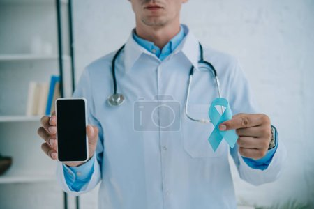 Photo for Cropped view of doctor holding blue awareness ribbon and smartphone with blank screen - Royalty Free Image