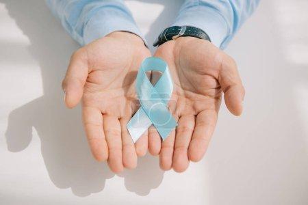 Photo pour Vue partielle des mains masculines avec ruban bleu de sensibilisation - image libre de droit