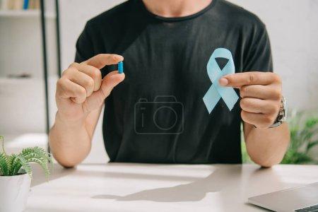 Photo pour Crocheté vue d'un homme en t-shirt noir tenant un ruban et une pilule de sensibilisation bleus - image libre de droit