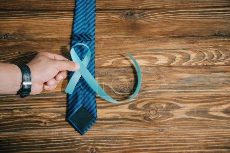 Photo pour Crochet vue d'un homme tenant un ruban bleu près d'une cravate sur une surface de bois - image libre de droit
