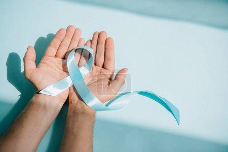 Photo pour Crochet vue des mains masculines avec ruban bleu sur fond blanc - image libre de droit