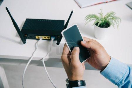 Foto de Vista recortada de los hombres de negocios que tienen teléfono inteligente cerca de un router conectado - Imagen libre de derechos
