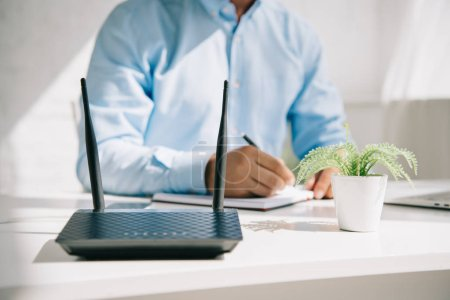 Foto de Cropped view of businessman writing in notebook near router and flowerpot - Imagen libre de derechos