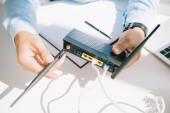"Постер, картина, фотообои ""cropped view of businessman adjusting antenna of router"""