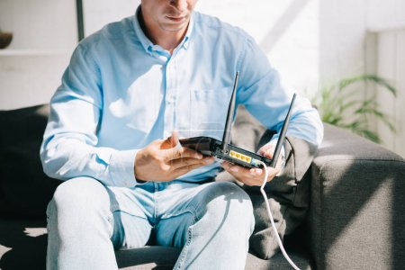 cropped view of businessman sitting on sofa and holding plugged router