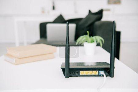 black plugged router on white table near books and flowerpot