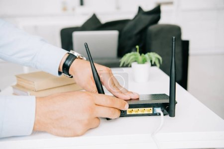 partial view of businessman adjusting router on white table