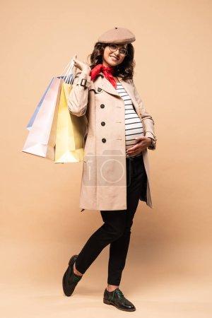 Photo pour Femme française enceinte en manteau tenant des sacs à provisions sur fond beige - image libre de droit