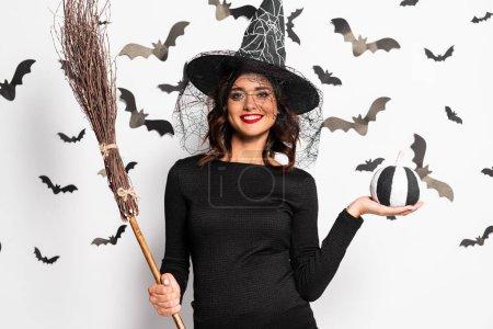 Photo pour Femme enceinte en chapeau de sorcière tenant balai et citrouille à Halloween - image libre de droit