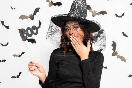 Photo pour Shocked woman in witch hat holding stick with lettering boo in Halloween - image libre de droit