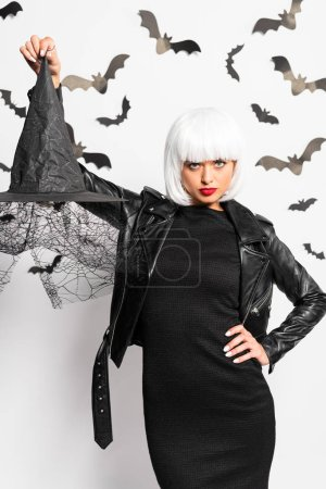 Photo pour Attractive woman in wig holding witch hat in Halloween - image libre de droit