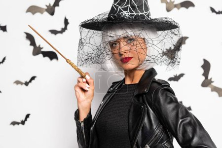 Photo pour Attractive woman in witch hat and wig holding magic wand in Halloween - image libre de droit