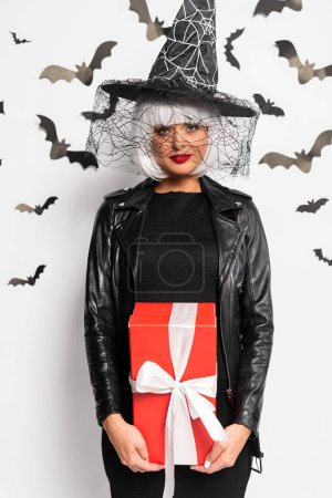 Photo pour Attractive woman in witch hat and wig holding gift in Halloween - image libre de droit