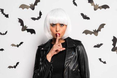 Photo pour Attractive woman in white wig showing shh gesture in Halloween - image libre de droit