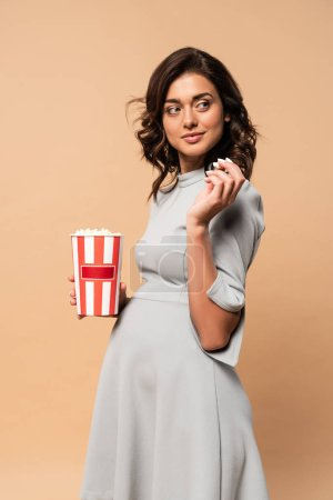 pregnant woman in grey dress holding popcorn on beige background