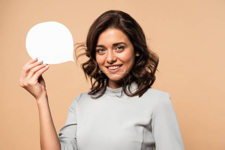 Photo for Smiling woman in grey dress holding speech bubble isolated on beige - Royalty Free Image
