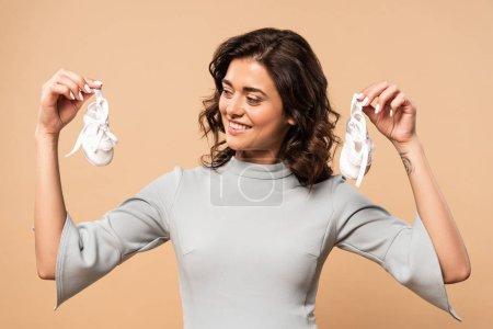 Photo pour Femme enceinte en robe grise tenant des chaussures sur fond beige - image libre de droit