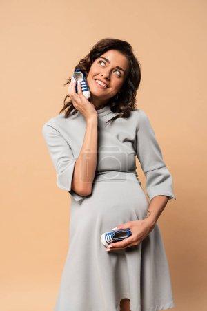 Photo pour Pregnant woman in grey dress holding sneakers on beige background - image libre de droit